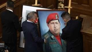 Dois homens penduram quadro com rosto do ex-presidente Hugo Chávez em uma parede