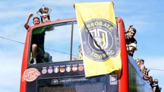Harrogate Town's Josh Falkingham holds the trophy as he celebrates with team-mates during an open top bus tour around Harrogate