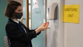 Secondary school pupil uses hand sanitiser