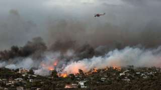 A firefighting helicopter flies over a wildfire raging in the town of Rafina.