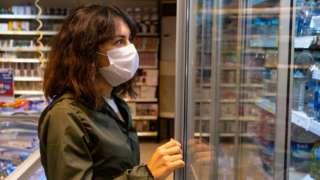امرأة ترتدي قناعا في متجر