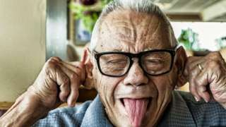 A elderly man pulling silly faces