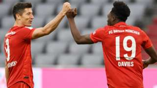 Robert Lewandowski (left) celebrates a Bayern Munich goal with team-mate Alphonso Davies