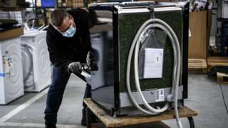 An employee inspects a washing-machine at the BSH electrical appliances