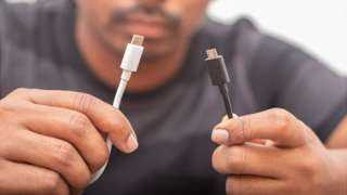 Un hombre con dos tipos de cables para dispositivos móviles