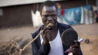 Un homme en train d'utiliser un bâtonnet frotte-dent