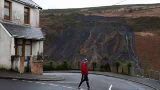 Man walks past house in Tylorstown, with coal tip landslide visible behind on hillside