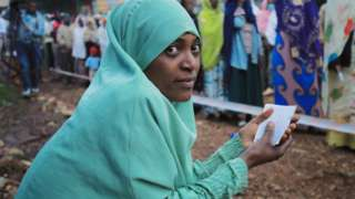 A woman waits to cast her vote at a polling station during the Ethiopian parliamentary and regional elections, in Beshasha, Ethiopia