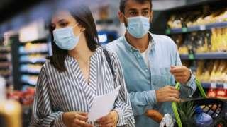 Casal faz compras no mercado durante pandemia