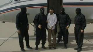 This frame grab released February 23, 2010 from Iranian state TV shows Sunni Muslim rebel leader Abdolmalek Rigi under armed guard following his arrest. Man is in handcuffs surrounded by four masked men, in front of a small plane