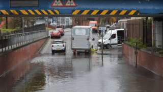 A road which passes under a rail bridge is flooded. Vehicles have been stopped by the water.