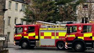 A fire engine is parked outside flats in East Kilbride