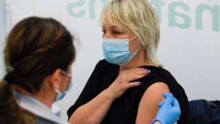 A woman receives a dose of Covid-19 vaccine in a vaccination centre at Newmarket Racecourse