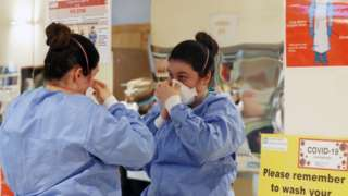 A healthcare worker placing a PPE mask on her face