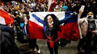 A woman holds a Chilean flag as she reacts to the referendum on a new Chilean constitution in Valparaiso, Chile, October 25, 2020.