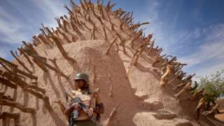 A soldier of the Malian army patrols the archaeological site of the Tomb of Askia in Gao on March 10, 2020.