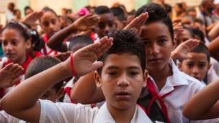 Cuban schoolchildren salute as they cry out loud the slogan 'Pioneers for Communism, we will be like Che!' on the first day of the 2013-2014 academic year, in Havana on September 2, 2013.
