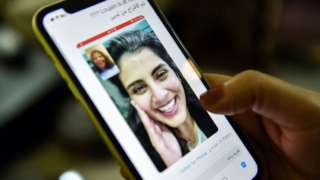 A woman looks at a tweet posted by the sister of Saudi activist Loujain al-Hathloul, showing a screenshot of them having a video call following her release from prison (10 February 2021)