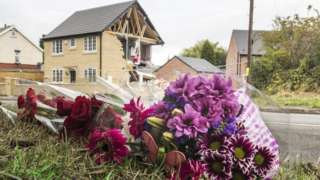Flowers on the ground with damaged house in the background