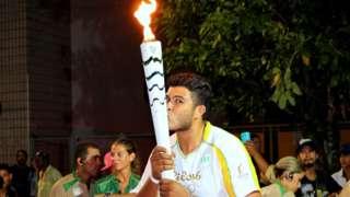 Ygor Marcel da Cruz Santos segura com as duas mãos e beija a tocha olímpica, vestido com o uniforme branco e amarelo utilizado pelos condutores nas Olimpíadas de 2016. Ao fundo, há outras pessoas e a folhagem de uma árvore