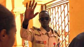 A security man in Sudan waves