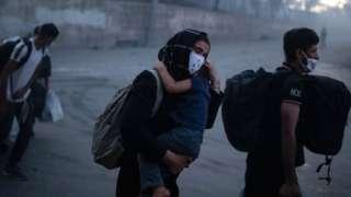 一位女士抱着一名男童逃离莫里亚营地(9/9/2020)