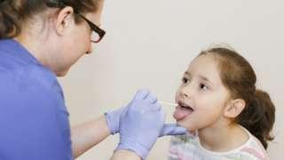 Nurse doing Covid test on child