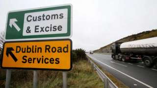 A tanker lorry travels past a roadside sign that reads: Customs & Excise