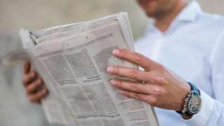 A stock photo shows a close-up of businessman reading newspaper