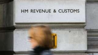 A woman walks past the HM Revenue and Customs building