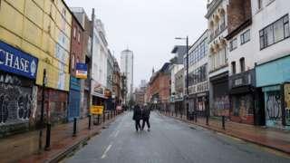 People walking down an empty street in Manchester