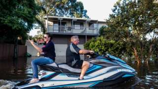People are seen on a jet-sky in a street affected by the flood on March 23, 2021 in Windsor, NSW
