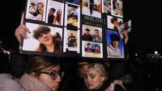 Friends of high school student Arad Zarei held pictures of him at a vigil for victims of the Iran plane crash in Toronto