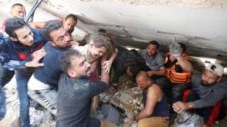 ဓါတ်ပုံ ၁။ ။ မေလ ၁၆ ရက်နေ့ အစ္စရေးရဲ့ လေကြောင်းတိုက်ခိုက်မှုကြောင့် ပြိုကျခဲ့တဲ့ အဆောက်အအုံ အပျက်အစီးများကြားက ကယ်ထုတ်နိုင်ခဲ့တဲ့ ကလေးငယ်
