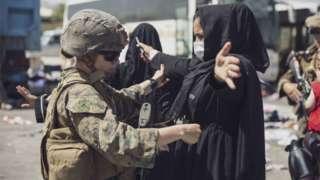 在哈米德卡爾扎伊國際機場,一名美國海軍陸戰隊員在撤離控制中心檢查一名婦女。