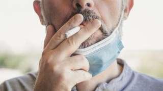 Homem fumando, com máscara contra a covid abaixada