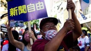 """中天电视的支持者手举""""新闻自由""""标牌表达抗议。"""