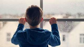 Stock image of a boy at a window