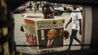 A man reads a newspaper with a headline announcing the death of Tanzania's President John Magufuli in Dar es Salaam, on March 18, 2021. - Tanzania was plunged into mourning on March 18, 2021 over the death of President John Magufuli following weeks of uncertainty over his health, with his swing to authoritarianism leaving a divided legacy.