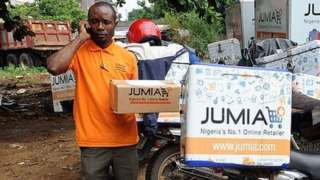 A Jumia scooterman tries to speak to clients to be delivered with product at the Ikeja warehouse of the company in lagos on June 12, 2013.