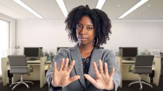 """A woman in her office stands with her hands out in front of her indicating """"no"""""""