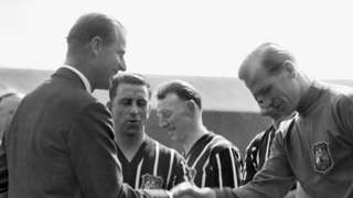 "The Duke of Edinburgh smiles while shaking hands with Manchester City""s Footballer of the Year Bert Trautmann, before the FA Cup final at Wembley"