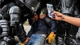 Colombian police officers arrest a demonstrator during a protest against the government in Cali, Colombia, on 10 May