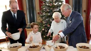 """Queen Elizabeth II, the Prince of Wales, the Duke of Cambridge and Prince George preparing special Christmas puddings in the Music Room at Buckingham Palace, London, as part of the launch of The Royal British Legion""""s Together at Christmas initiative"""