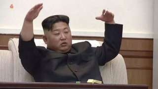 Kim Jong-un gestures with a cigarette in his hand