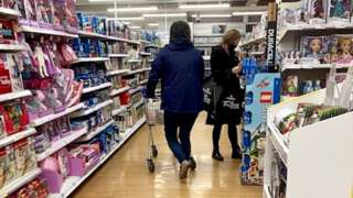 People shopping in supermarket aisle