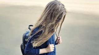 A girl walking with her head down