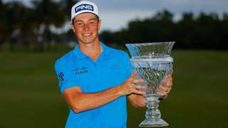 Viktor Hovland smiles as he holds up the Puerto Rico Open trophy