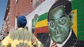 A man stands next to a mural of Robert Mugabe
