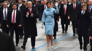 President Donald Trump and First Lady Melania Trump wave during the inauguration parade in Washington.